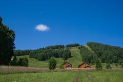 Twee houten hotels dichtbij heuvel Stock Foto