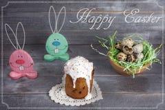 Twee houten konijn, een nest met kwartelseieren en Pasen-cakes met stock afbeeldingen
