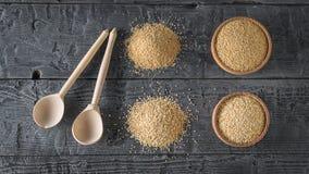 Twee houten lepels, amarantzaden, quinoa zaden op een zwarte houten lijst Het vrije voedsel van het gluten stock foto's