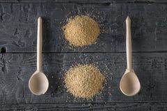 Twee houten lepels, een bos van amarantzaden en een bos van quinoa zaden op een donkere houten lijst Het vrije voedsel van het gl royalty-vrije stock afbeelding