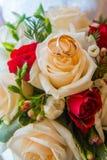 Twee huwelijks gouden ringen met diamanten zijn op bride& x27; s boeket van rode en witte rozen stock afbeelding