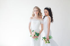 Twee huwelijksbruid met een boeket van het haar van het bloemenhuwelijk stock foto