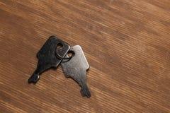 Twee ijzersleutels op een houten oppervlakte stock foto