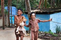 Twee Indische jongens met hond op de straat in de visserij van dorp Royalty-vrije Stock Fotografie