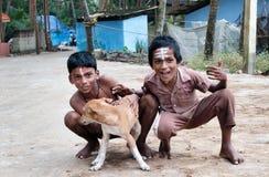 Twee Indische jongens met hond op de straat in de visserij van dorp Stock Foto's