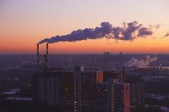Twee industriële buizen, de mening van de zonsopgangstad, doorboren warme hemel Stock Foto