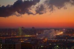 Twee industriële buizen, de mening van de zonsopgangstad, doorboren warme hemel Royalty-vrije Stock Foto