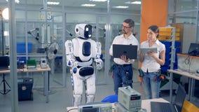 Twee ingenieurs controleren ver acties van een cyborg met computers stock video