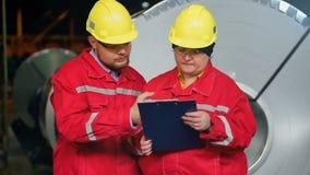 Twee ingenieurs die bespreking over industriële staalfabriek hebben stock videobeelden