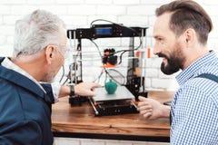 Twee ingenieurs drukken een appelmodel op een 3d printer Zij bekijken het resultaat van het werk van de 3d printer Royalty-vrije Stock Afbeeldingen