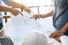 Twee ingenieursbespreking over architecturaal project bij bouwwerf op modern kantoor stock foto