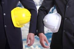 Twee Ingenieursmensen die veiligheidshoed houden stock afbeeldingen
