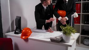 Twee ingenieurszakenlieden bekijken architectentekening met helm stock footage