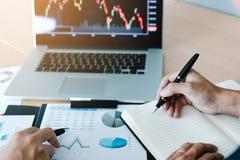 Twee investeerders werken en nemen nota van de voorraadprijs samen om met andere voorraden vergelijkbaar te zijn royalty-vrije stock afbeelding