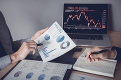 Twee investeerders werken samen met het analyseren van de grafieken van voorraadgegevens in het document en het bekijken van de g royalty-vrije stock foto