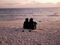 Twee Islamitische meisjes in burkini letten op de zonsondergang in de Maldiven royalty-vrije stock fotografie