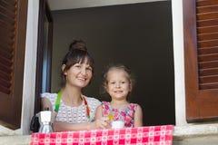 Twee jaar oude dochter met haar het drinken zitting van de koffiemoeder dichtbij open venster met traditionele Europese houten br Stock Foto's