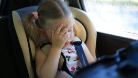 Twee-jaar-oude meisjeszitting in de auto in de de autozetel van de kinderen het schreeuwen en zeer verstoord stock videobeelden