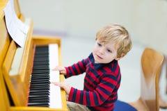 Twee jaar oude peuterjongen het spelen piano, muziekschoool Royalty-vrije Stock Foto's