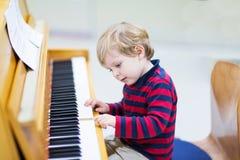 Twee jaar oude peuterjongen het spelen piano, muziekschoool Stock Foto's