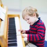 Twee jaar oude peuterjongen het spelen piano, muziekschoool Royalty-vrije Stock Afbeeldingen