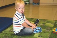 Twee jaar van de kindjongen het spel met auto's Onderwijsspeelgoed voor kleuterschool en kleuterschoolkind, binnenspeelplaats, le stock afbeeldingen
