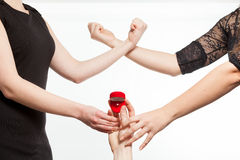 Twee jaloersheidsmeisjes die voor een ring vechten die door de mens worden gehouden Stock Afbeelding