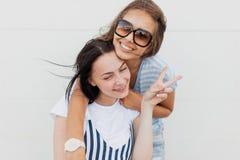 Twee jeugdige donker-haired meisjes, die toevallige uitrusting, mooie omhelzing dragen elkaar en bekijkend de camera royalty-vrije stock afbeeldingen