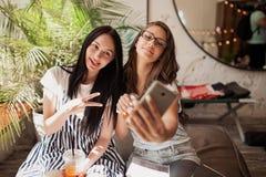 Twee jeugdige glimlachende mooie slanke meisjes met lang donker haar, die vrijetijdskleding dragen, zitten naast elkaar en nemen  stock fotografie