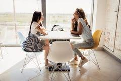 Twee jeugdige vrij slanke meisjes met donker haar, die toevallige uitrusting dragen, zitten bij de lijst naast elkaar en praatje  royalty-vrije stock fotografie