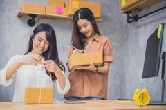 Twee jong Aziatisch mensen start kleine bedrijfsondernemerskleine/middelgrote ondernemingen distributiepakhuis met pakketbrievenb Stock Fotografie