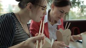 Twee jong bedrijfsmeisje voor lunch die Chinese noedels eten en koffie drinken, die de ontwikkeling van zaken onderzoeken stock videobeelden