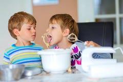 Twee jong geitjejongens die cake in binnenlandse keuken bakken royalty-vrije stock fotografie