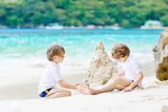Twee jong geitjejongens die zandkasteel bouwen op tropisch strand stock fotografie