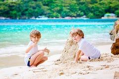Twee jong geitjejongens die zandkasteel bouwen op tropisch strand royalty-vrije stock foto's