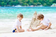 Twee jong geitjejongens die zandkasteel bouwen op tropisch strand stock foto's