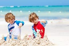 Twee jong geitjejongens die zandkasteel bouwen op tropisch strand van Playa del Carmen, Mexico royalty-vrije stock fotografie