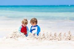 Twee jong geitjejongens die zandkasteel bouwen op tropisch strand van Playa del Carmen, Mexico royalty-vrije stock foto's