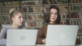 Twee jong studenten vriendschappelijk wijfje en mannetje die een dalogue in de bibliotheek hebben stock video