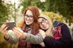 Twee jong studentenmeisje met lang haar en glazen het lopen royalty-vrije stock afbeelding