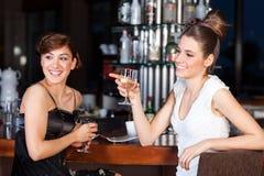 Twee jong vrouwen drinkwater bij staaf stock foto's