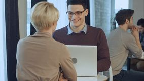 Twee jong zakenlui die laptop in hal van modern bureau met behulp van Royalty-vrije Stock Foto