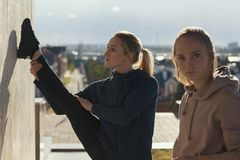 Twee jonge aantrekkelijke vrouwen die acrobatiek met cityscape op achtergrond doen royalty-vrije stock afbeelding