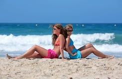 Twee jonge aantrekkelijke vrouwen die in de zon op vakantie koelen of vac Stock Foto's