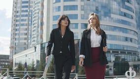 Twee jonge aantrekkelijke vrouwen in formele kostuums gaan tegen de achtergrond van een modern commercieel centrum stock video