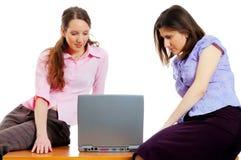 Twee jonge aantrekkelijke vrouwen met een computer stock fotografie