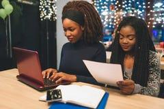 Twee jonge Afrikaanse vrouwenstudie bij lijst in koffie Eerste type op toetsenbordlaptop Tweede bekijkt stuk van document Zij zij royalty-vrije stock foto's