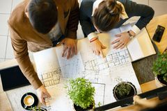 Twee jonge architecten die bouwtekeningen bespreken tijdens een vergadering in een bureau stock afbeeldingen