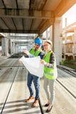 Twee jonge architecten die grote bouwwerf bezoeken, die plattegronden bekijken stock fotografie