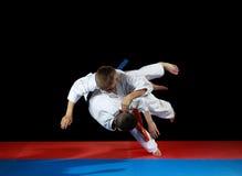 Twee jonge atleten in de scherpe daling voeren judo uit werpen Royalty-vrije Stock Fotografie
